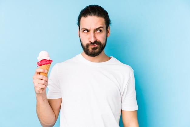 孤立したアイスクリームを食べる若い白人男性は混乱しており、疑わしく感じています。