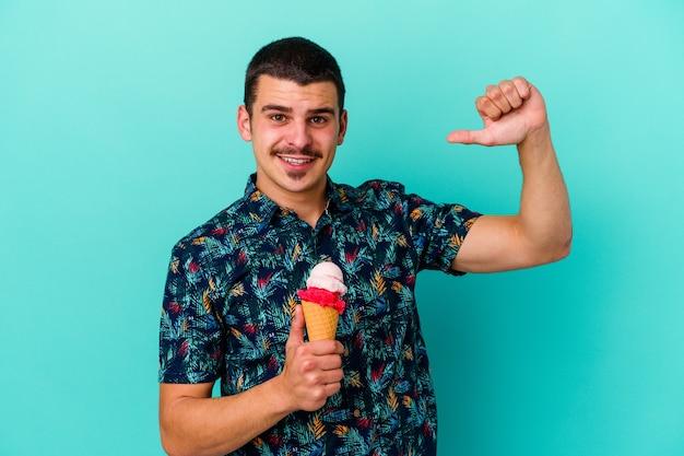 青い壁に隔離されたアイスクリームを食べる若い白人男性は、誇りと自信を持って、従うべき例を感じます