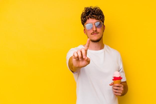손가락으로 번호 하나를 보여주는 노란색 배경에 고립 된 아이스크림을 먹는 젊은 백인 남자.