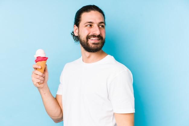 Молодой человек кавказской, едят мороженое смотрит в сторону, улыбаясь, веселый и приятный.