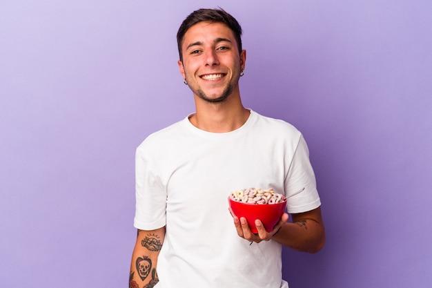 紫色の背景に分離されたシリアルを食べる若い白人男性は幸せ、笑顔、陽気な。