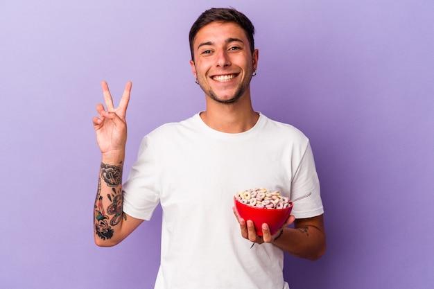 指で平和のシンボルを示す、楽しくてのんきな紫色の背景に分離された穀物を食べる若い白人男性。