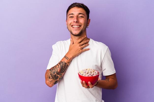 Молодой кавказский человек ест хлопья, изолированные на фиолетовом фоне, громко смеется, держа руку на груди.