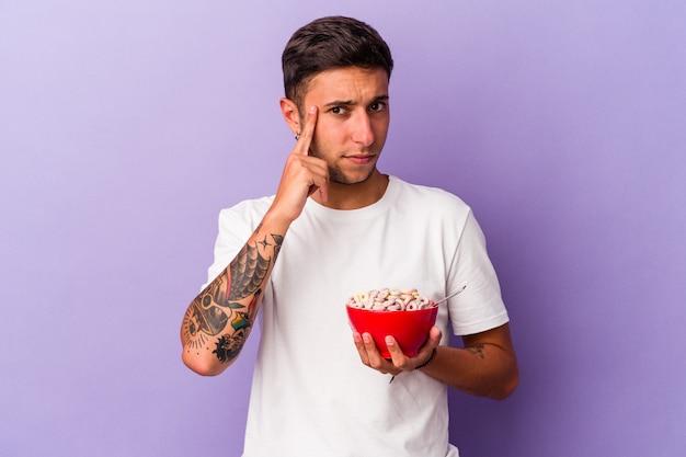 指で寺院を指し、思考、タスクに焦点を当て、紫色の背景に分離された穀物を食べる若い白人男性。