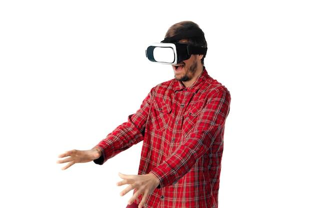 Giovane uomo caucasico che gioca emotivo, utilizzando l'auricolare per realtà virtuale isolato su sfondo bianco per studio. concetto di moderne tecnologie, gadget, tecnologia, emozioni umane, pubblicità. copyspace. ar, vr.