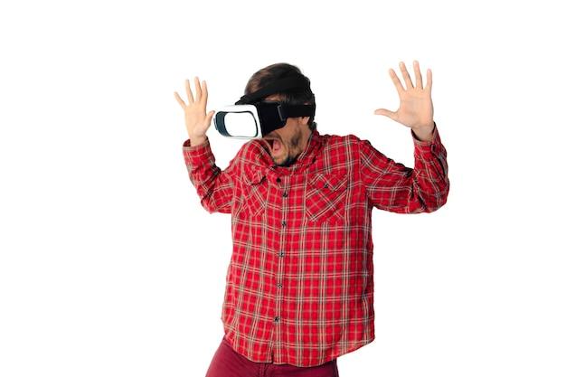 Молодой человек кавказской эмоциональной игры, используя изолированную гарнитуру виртуальной реальности.