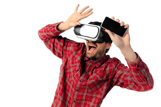 Giovane uomo caucasico che gioca emotivo, utilizzando cuffie da realtà virtuale e smartphone isolati su sfondo bianco per studio. concetto di moderne tecnologie, gadget, tecnologia, emozioni umane, pubblicità. copyspace.