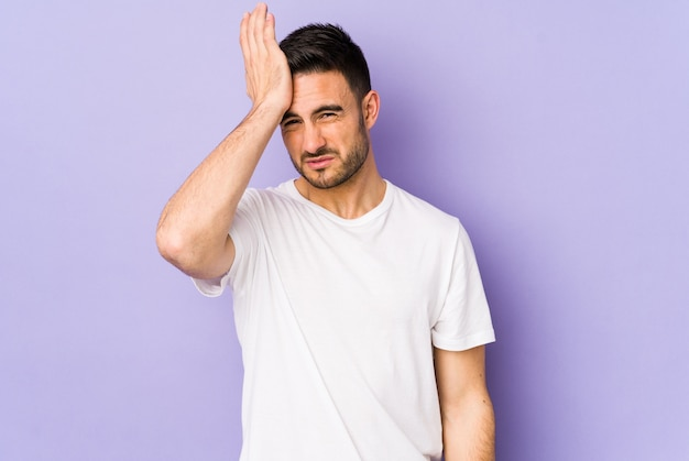 Young caucasian man forgetting something, slapping forehead with palm and closing eyes.