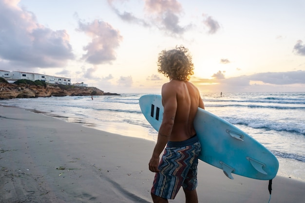 Young caucasian man get up early to  doing surf at sunrise