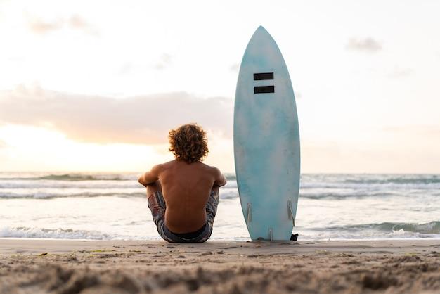 젊은 백인 남자는 일출에서 서핑을 일찍 일어나