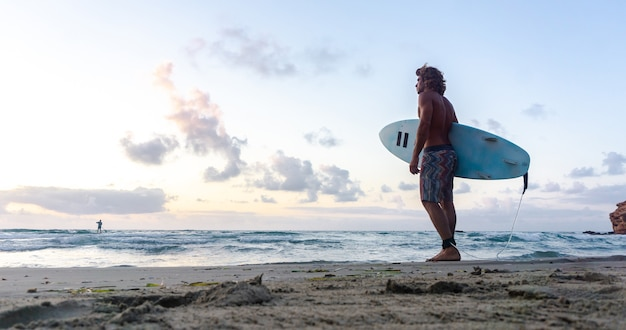 Молодой кавказский мужчина встает рано, чтобы заняться серфингом на рассвете