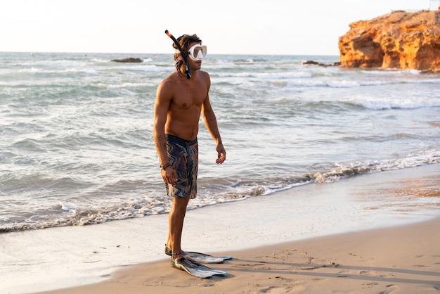 Молодой кавказский человек готовится погрузиться в море