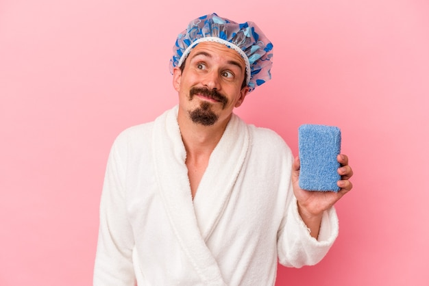 Young caucasian man going to the shower holding sponge isolated on pink background dreaming of achieving goals and purposes