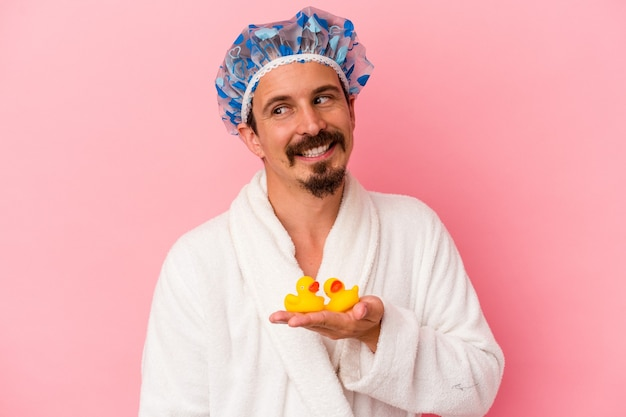 Young caucasian man going to the shower with rubber ducks isolated on pink background looks aside smiling, cheerful and pleasant.