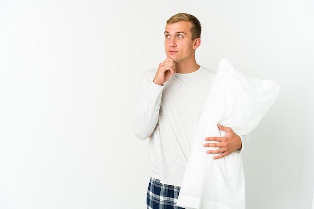 疑わしいと懐疑的な表現で横向きに見える白い背景に孤立して眠りにつく若い白人男性。