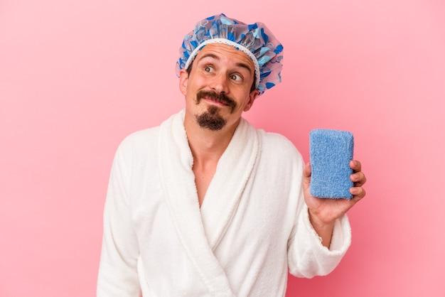 Молодой кавказский мужчина идет в душ с губкой на розовом фоне и мечтает о достижении целей и задач