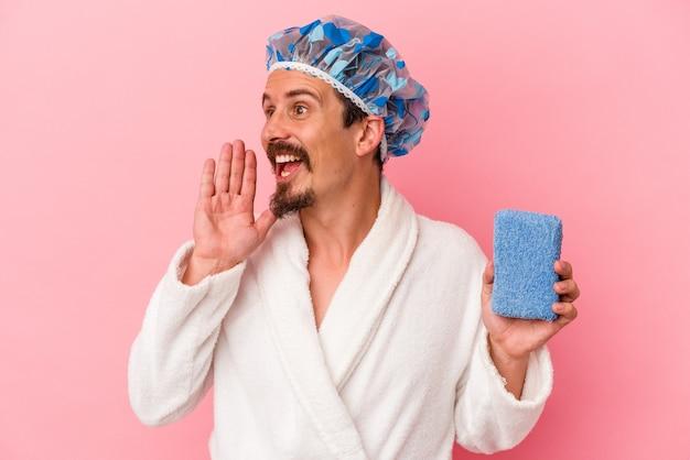 ピンクの背景に分離されたスポンジを持ってシャワーを浴びに行く若い白人男性が叫び、開いた口の近くで手のひらを保持します。