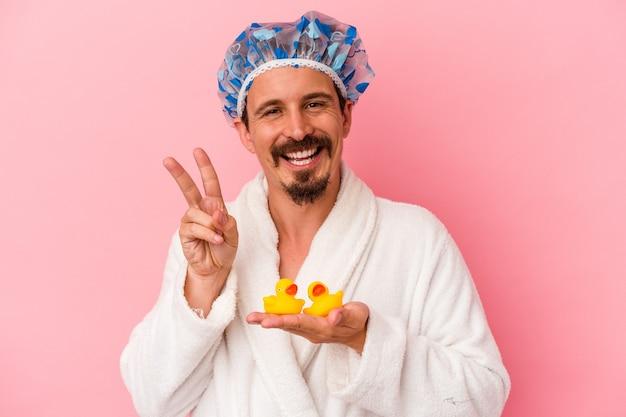 ピンクの背景に分離されたゴム製のアヒルとシャワーに行く若い白人男性は、指で平和のシンボルを喜んで気楽に示しています。