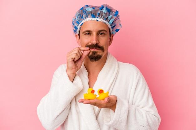 秘密を守って唇に指でピンクの背景に分離されたゴム製のアヒルとシャワーに行く若い白人男性。