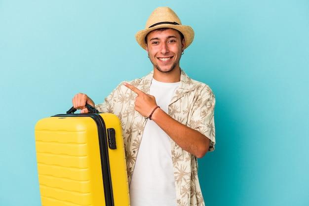 젊은 백인 남자는 푸른 배경에 고립되어 웃고 옆으로 가리키며 빈 공간에 무언가를 보여주며 여행할 것입니다.