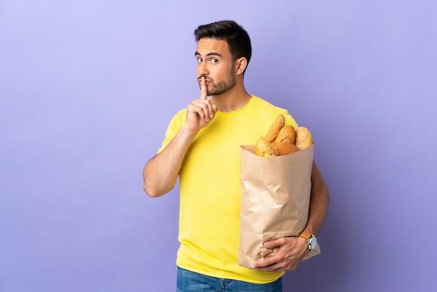 침묵 제스처를 하 고 보라색 배경에 고립 된 빵으로 가득한 가방을 들고 젊은 백인 남자