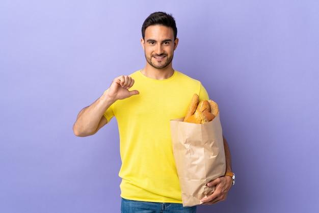 誇らしげで自己満足の紫色の背景に分離されたパンでいっぱいのバッグを保持している若い白人男性