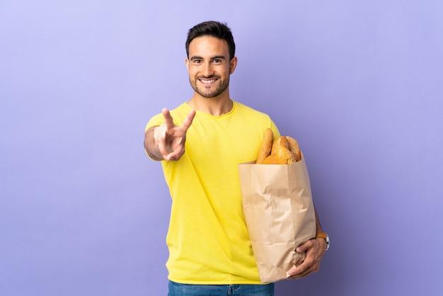 Молодой кавказский мужчина держит сумку, полную хлеба, изолированную на фиолетовой стене, улыбается и показывает знак победы