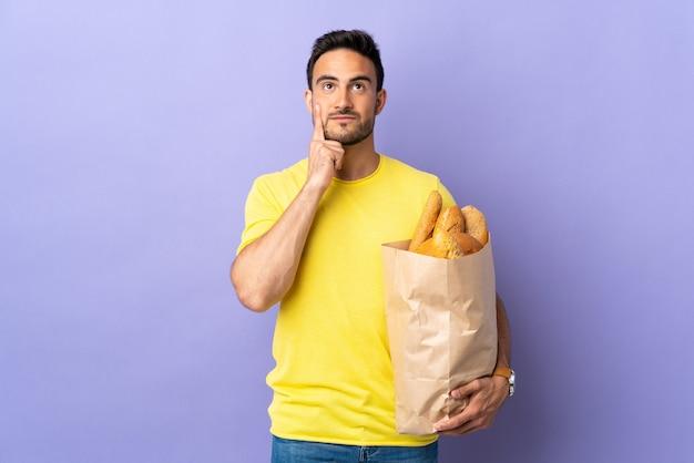 アイデアを考えて紫色の壁に分離されたパンでいっぱいのバッグを保持している若い白人男性