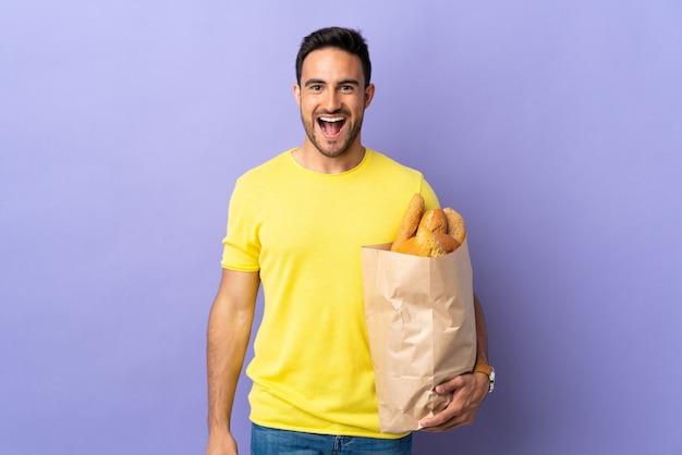 Молодой кавказский мужчина держит сумку, полную хлеба, изолированную на фиолетовой стене с удивленным выражением лица