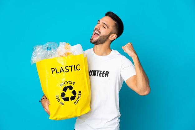 플라스틱 병으로 가득 찬 가방을 들고 젊은 백인 남자는 승리를 축하하는 파란색 배경에 고립 재활용