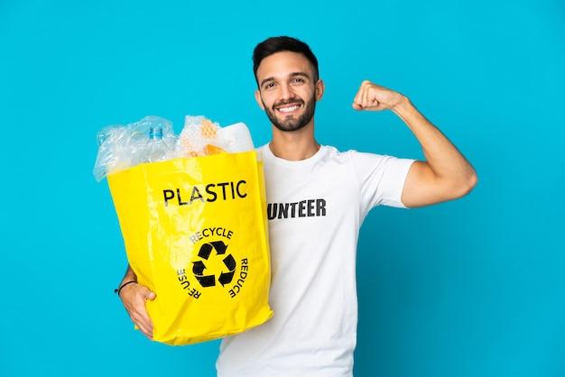 강한 제스처를 하 고 파란색 배경에 고립 된 재활용 플라스틱 병의 전체 가방을 들고 젊은 백인 남자