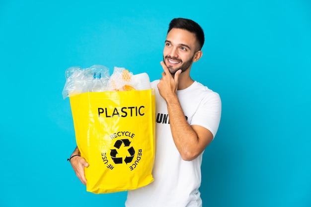 Молодой кавказский мужчина держит сумку, полную пластиковых бутылок для переработки, изолирован на синем фоне, думая об идее, глядя вверх