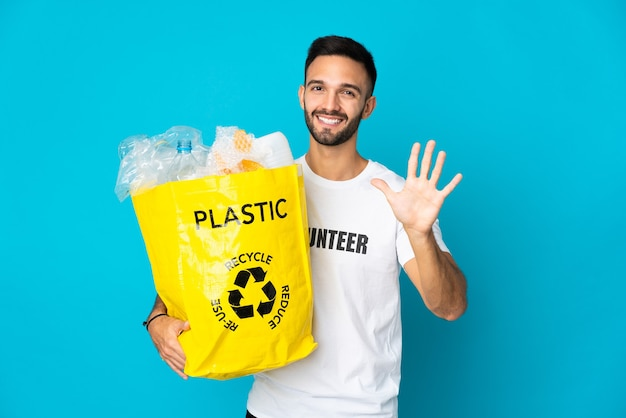 플라스틱 병으로 가득 찬 가방을 들고 젊은 백인 남자가 손가락으로 5 세를 세는 파란색 벽에 고립 된 재활용