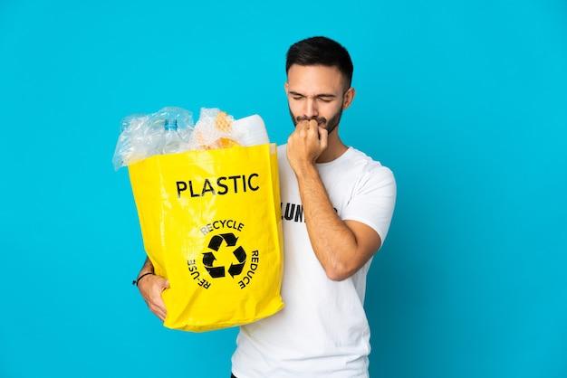 Молодой кавказский мужчина держит сумку, полную пластиковых бутылок для переработки, изолирован на синей стене, сомневаясь