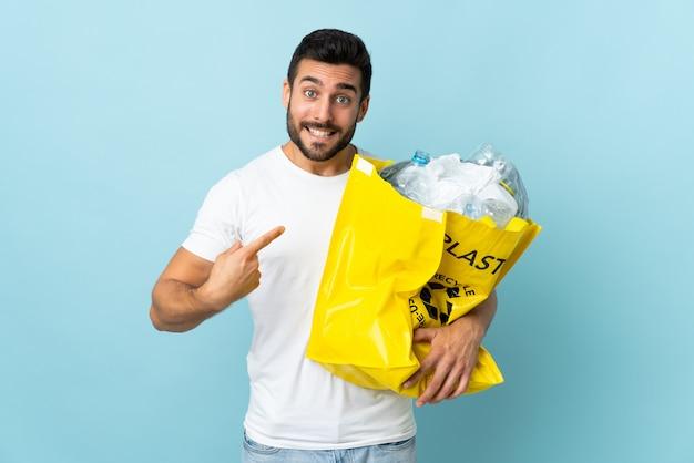 Молодой человек кавказской, держа сумку, полную пластиковых бутылок для переработки, изолированные на голубой стене с удивлением выражение лица