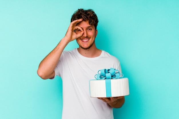 파란색 배경에 고립 된 케이크를 들고 젊은 백인 남자 눈에 확인 제스처를 유지 흥분.