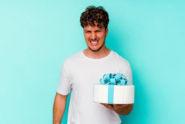 Молодой кавказский человек, держащий торт, изолированный на синем фоне, кричит очень сердито и агрессивно.