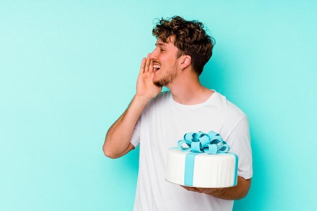 青の背景に分離されたケーキを持った若い白人男性が叫び、開いた口の近くに手のひらを保持しています。