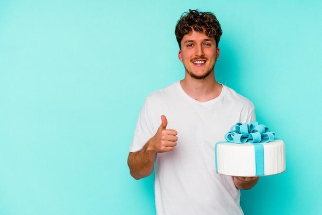 파란색 배경에 고립 된 케이크를 들고 젊은 백인 남자가 웃고 엄지 손가락을 올리는