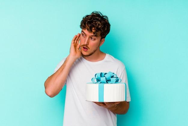 ゴシップを聴こうとしている青い背景で隔離のケーキを保持している若い白人男性。