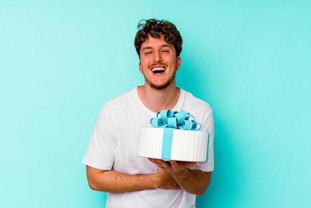 笑って楽しんで青い壁に分離されたケーキを保持している若い白人男性。
