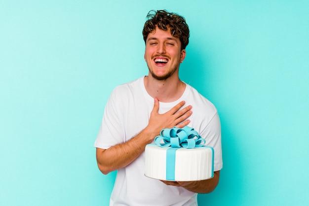 青い壁に隔離されたケーキを持っている若い白人男性は、胸に手を置いて大声で笑います。