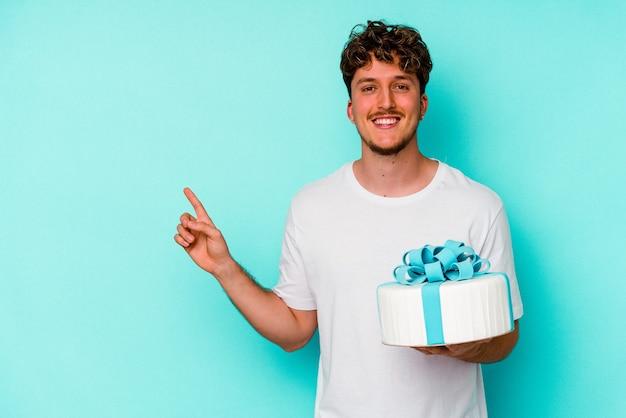 青い壁に隔離されたケーキを持って笑顔で脇を指して、空白のスペースで何かを示している若い白人男性。