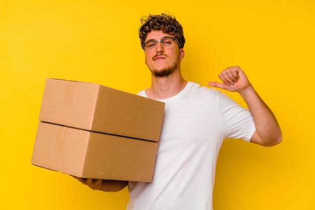 黄色の背景に分離された段ボール箱を持っている若い白人男性は、誇りと自信を持って感じています。