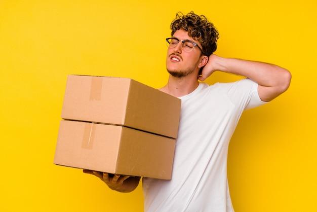 頭の後ろに触れて、考えて、選択をする黄色の背景に分離された段ボール箱を保持している若い白人男性。