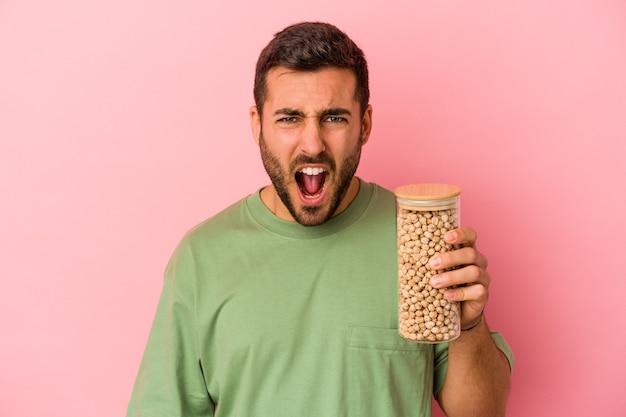 Молодой кавказский мужчина держит бутылку нута, изолированную на розовом фоне, кричит очень сердито и агрессивно.