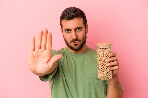 ピンクの背景に分離されたひよこ豆のボトルを保持している若い白人男性は、一時停止の標識を示している手を伸ばして立って、あなたを防ぎます。
