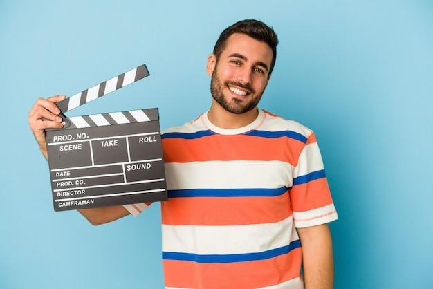Молодой кавказский человек, держащий с 'хлопушкой', изолированные на синем фоне, счастлив, улыбается и весел.