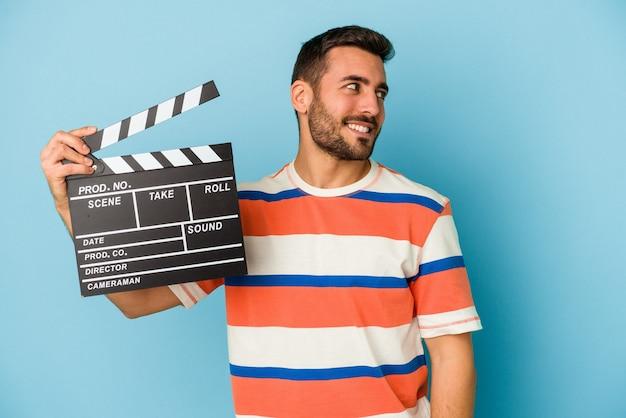 青の背景にカチンコを持った若い白人男性は、笑みを浮かべて、陽気で快適に見えます。