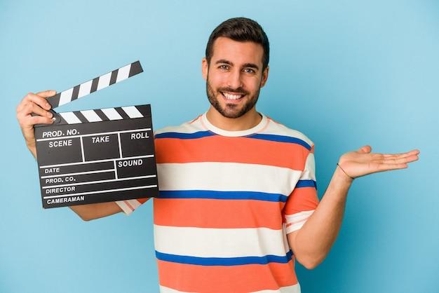 青い背景に分離されたカチンコを持ち、手のひらにコピー スペースを表示し、腰に別の手を保持している若い白人男性。